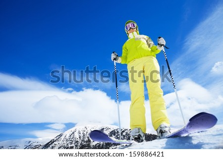 Happy young woman skier stand on top of the mountain and ready to go downhill - wide angle shoot with copy space - stock photo