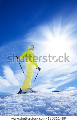 Happy young woman skier stand on top of the mountain on bright sunny day - stock photo