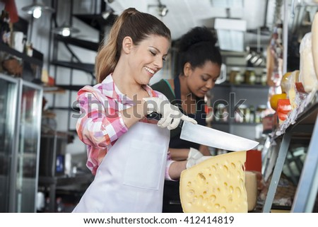 Happy Young Woman Slicing Cheese With Knife In Shop - stock photo