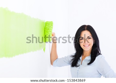 happy young woman smile paint in green color home white wall of new apartment, female hold roller brush repair house decor - stock photo