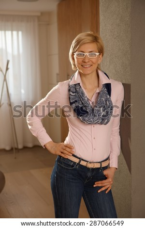 Happy young woman smiling at home, looking at camera. - stock photo