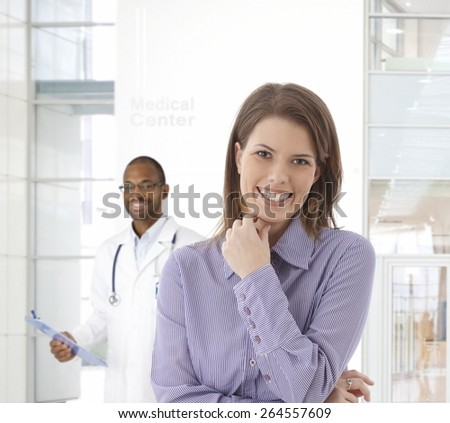Happy young woman smiling at medical center, looking at camera, doctor standing at background. - stock photo