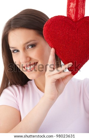 Happy young woman smiling at valentine's day, holding a red heart.