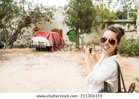 Happy young woman smiling while taking snapshot with cell phone camera the vintage grunge old car in the messy place in the city in Tel Aviv. Unusual moment from vocation or travel. - stock photo