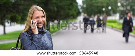 happy young woman speaks by phone on the street - stock photo
