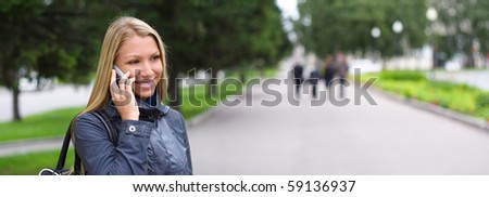 happy young woman speaks by phone on the street