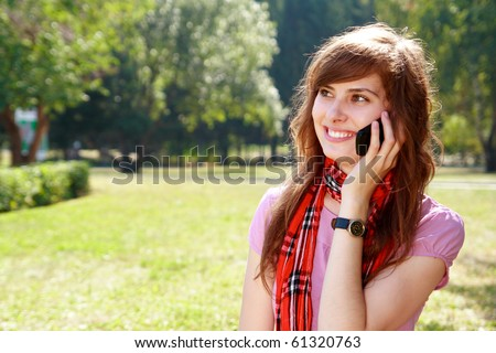happy young woman speaks by phone outdoors