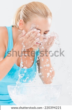 Happy young woman splashing water over her face. - stock photo