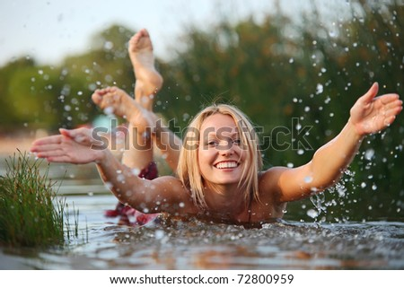 Happy young woman splashing water while swimming - stock photo