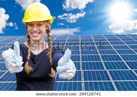 Happy young woman standing in front of solar panels - stock photo