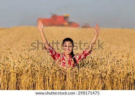 Happy young woman standing in golden wheat field during harvest - stock photo