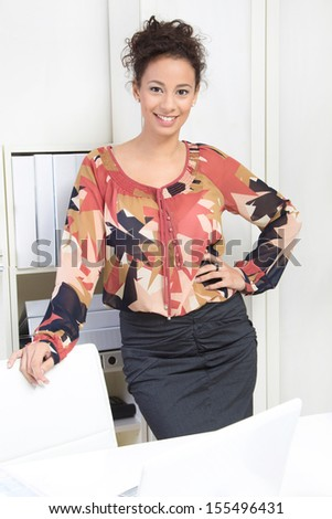 Happy young woman standing in office