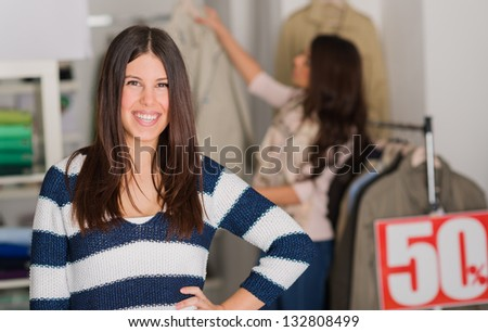 Happy Young Woman Standing In Shopping Mall, Indoors