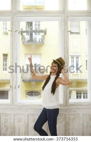 Happy young woman standing in window, having fun. - stock photo
