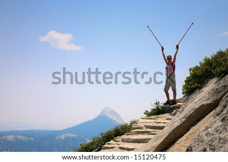 Happy young woman standing  on top of a mountain with arms raised - stock photo