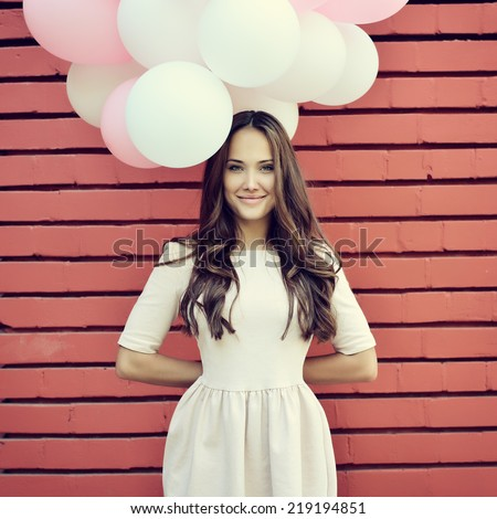 Happy young woman standing over red brick wall and holding pink and white balloons. Pleasure. Dreams. Toned. - stock photo