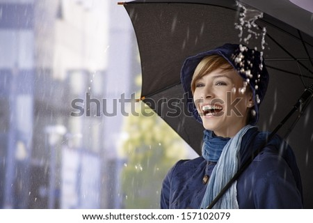 Happy young woman standing under umbrella in rain, laughing. - stock photo