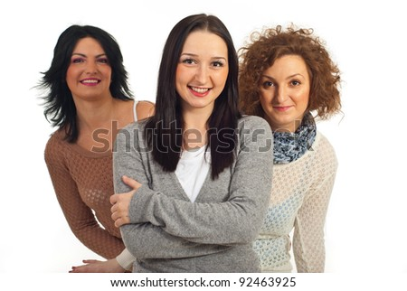 Happy young woman standing with arms folded and her friends smiling from her back against white background - stock photo
