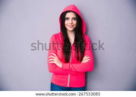Happy young woman standing with arms folded over gray background. Looking at camera. - stock photo