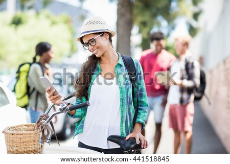 Happy young woman standing with bicycle using mobile phone - stock photo