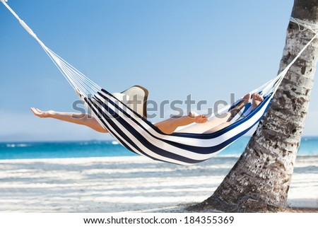 Happy young woman stretching in hammock at beach - stock photo
