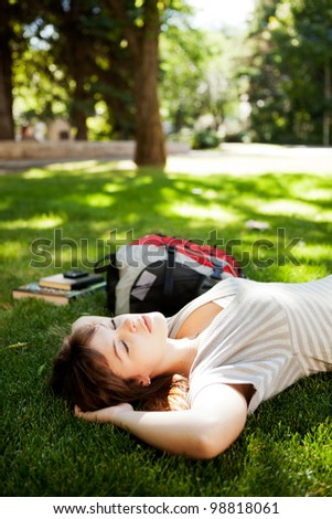 Happy young woman student laying on grass and dreaming about future