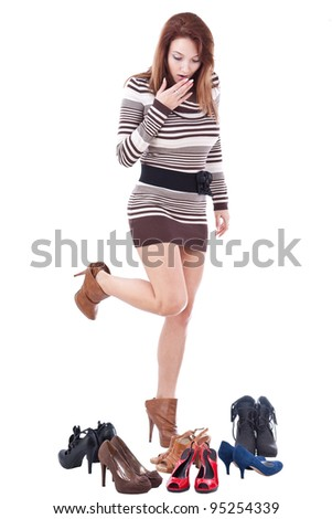 Happy young woman surrounded by all of her shoes - stock photo