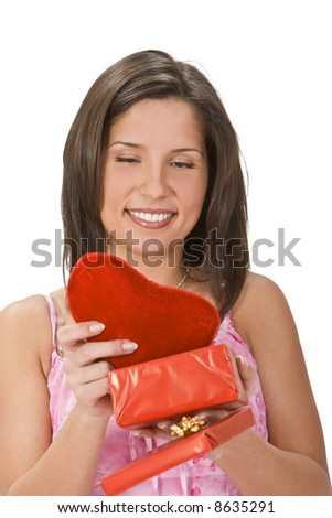 Happy young woman taking a plush heart out of a red gift box. - stock photo