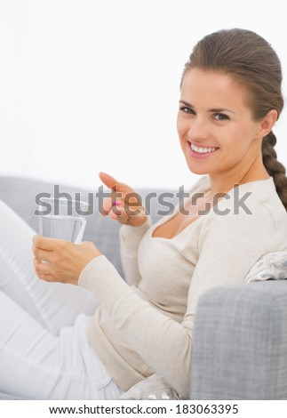 Happy young woman taking pill - stock photo