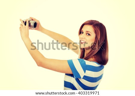 Happy young woman taking selfie with classic slr camera - stock photo