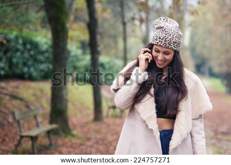 Happy young woman talking at the phone outdoors in a park.