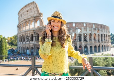 Happy young woman talking cell phone in front of colosseum in rome, italy - stock photo