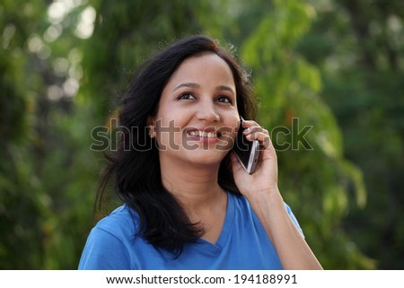 Happy young woman talking on mobile phone at outdoors - stock photo