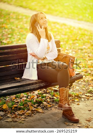 Happy young woman talking on phone in Autumn park - stock photo