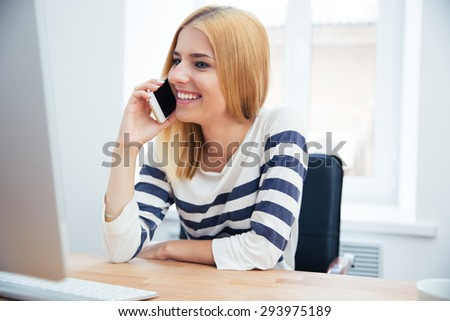 Happy young woman talking on the phone in office