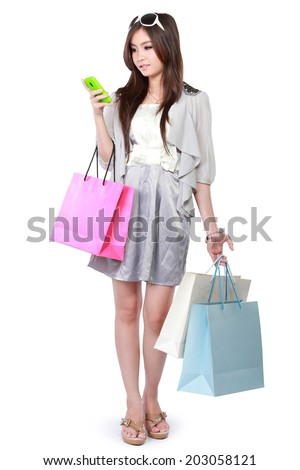 happy young woman texting on cellphone while shopping