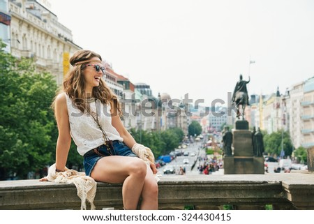 Happy young woman tourist in boho chic clothes relaxing on parapet in the historical center of Prague. In the background Saint Wenceslas statue on Wenceslas Square in Prague. Tourism travel concept.