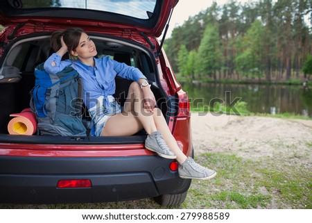 Happy young woman tourist travel on a red car to summer forest. Holiday trip to lake - stock photo