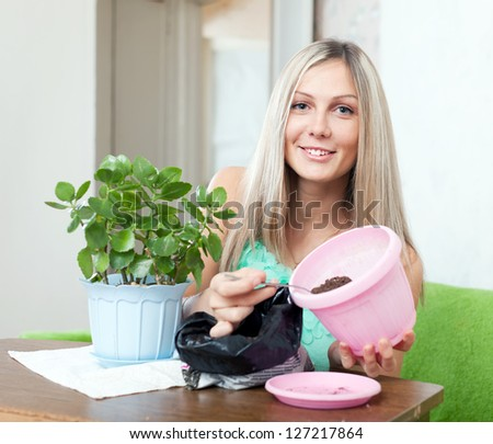Happy young woman transplants Kalanchoe in flowerpot at home