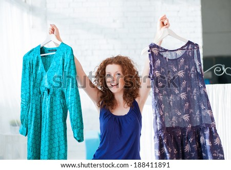 Happy young woman trying clothing dress - stock photo