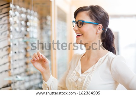 Happy young woman trying new glasses at optician store - stock photo