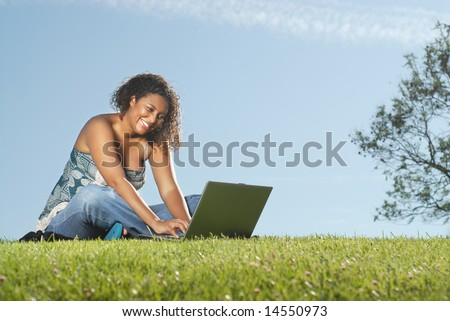 Happy young woman typing away on a laptop while sitting outside - stock photo
