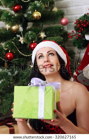 happy young woman under a Christmas tree holding Christmas gift - stock photo