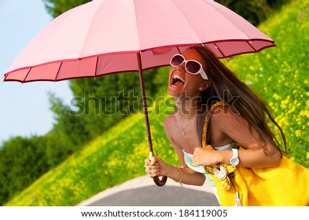Happy young woman under pink umbrella in summer day (face in the shade of umbrella). Girl looking up at sky smiling cheerful.  - stock photo