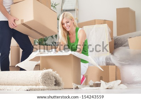 Happy young woman unpacking boxes in new home - stock photo