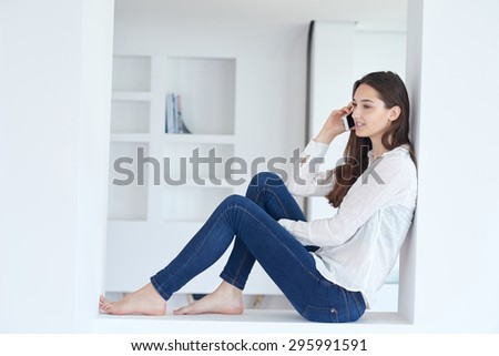happy young woman using cellphone at home and relaxing - stock photo