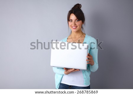 Happy young woman using her laptop - stock photo