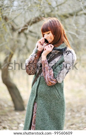 Happy young woman using mobile phone outdoors - stock photo