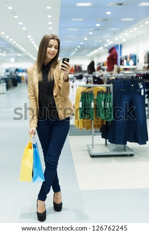 Happy young woman using smart phone in shopping mall - stock photo
