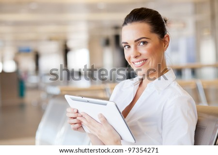 happy young woman using tablet computer at airport - stock photo